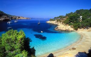 cala-salada-ibiza-pine-forested-hills-little-cove-beach-boat-nature